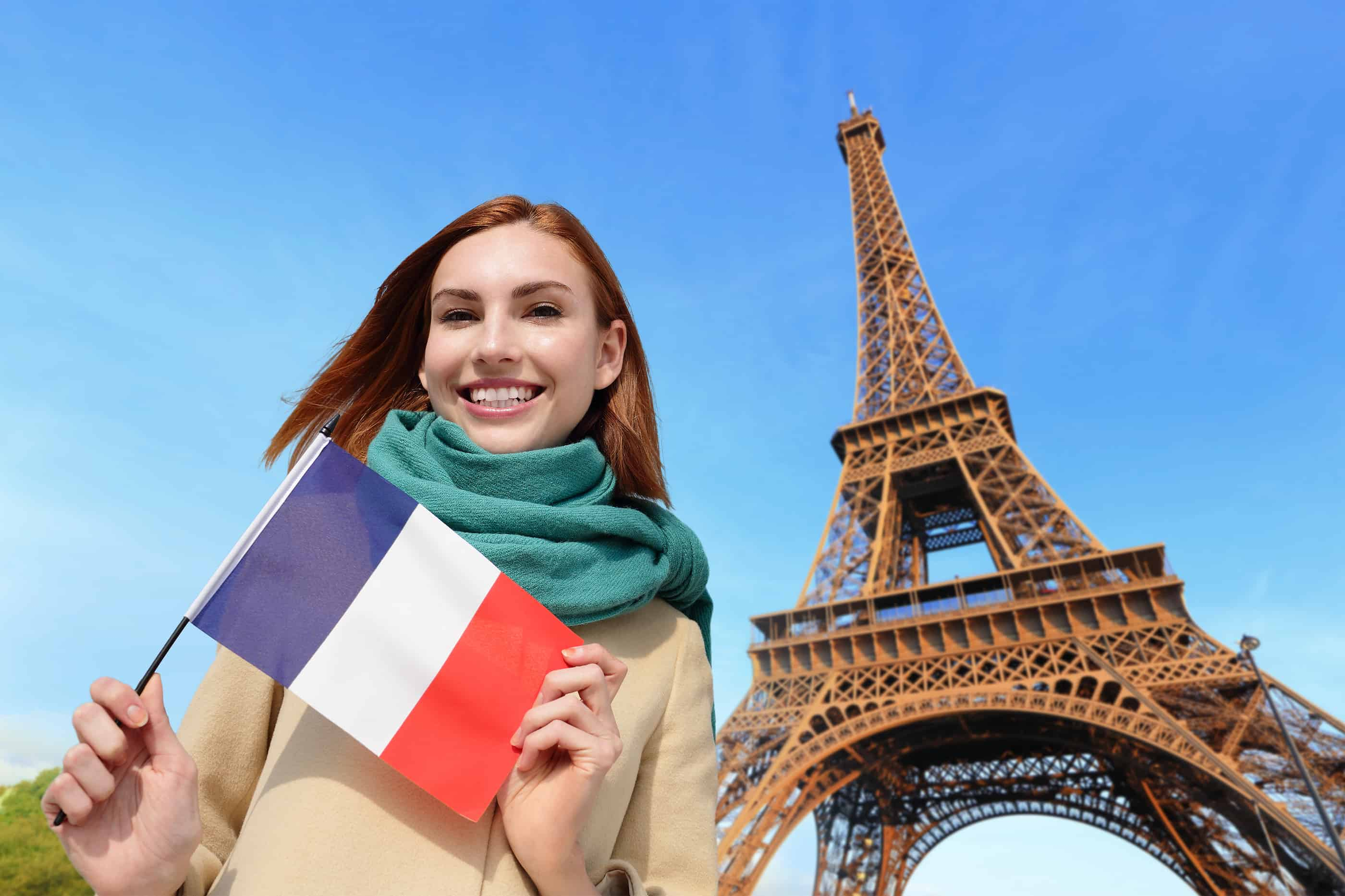 Happy woman travel in Paris with eiffel tower and beautiful blue sky and holding France French flag caucasian beauty