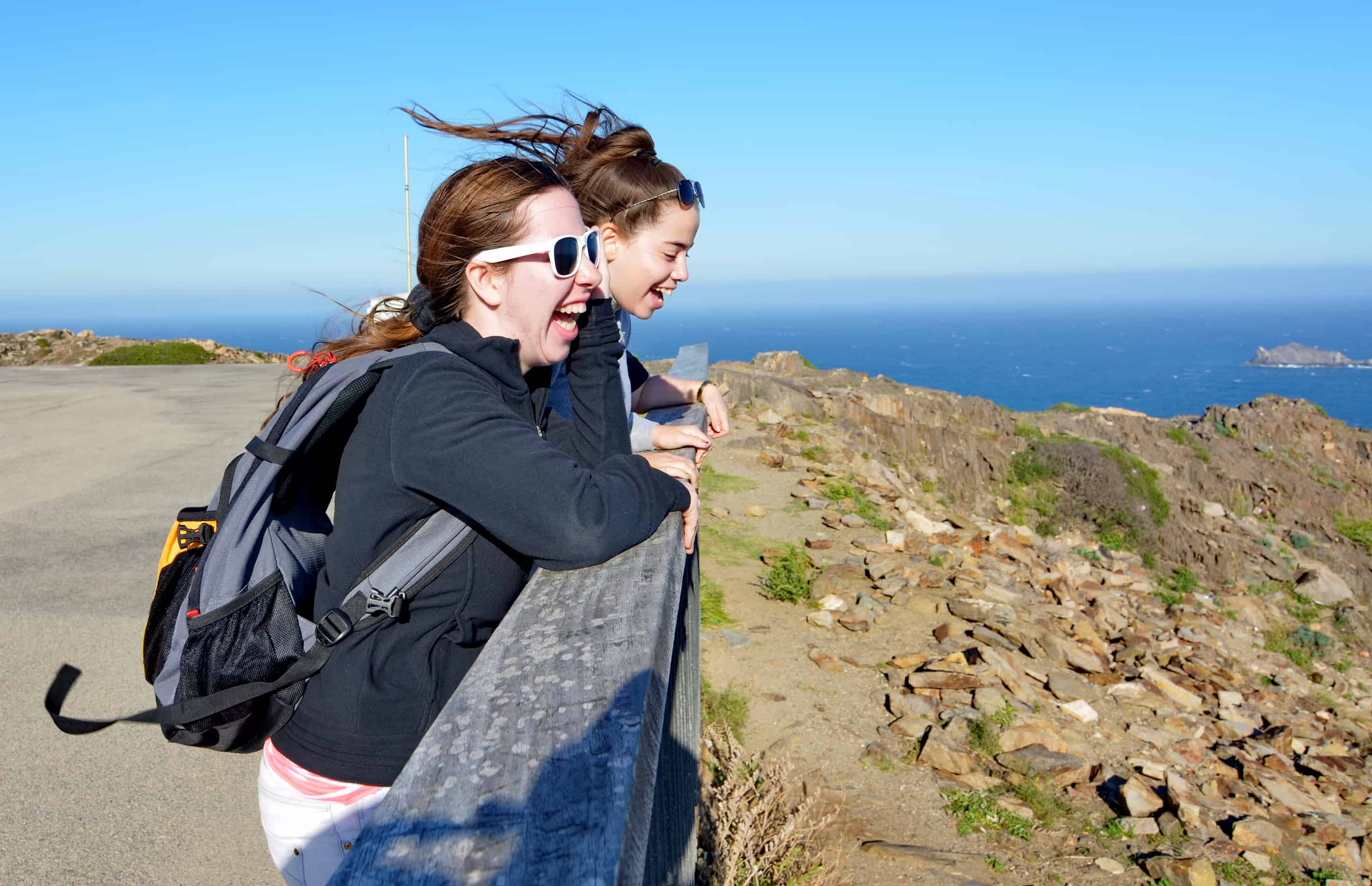 Two teenage sisters enjoying the view and strong northen winds at Cap de Creus Costa Brava Spain